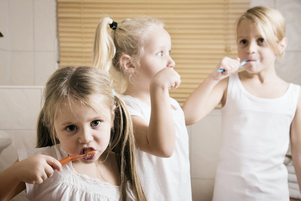 Three young girls brushing their teeth at home