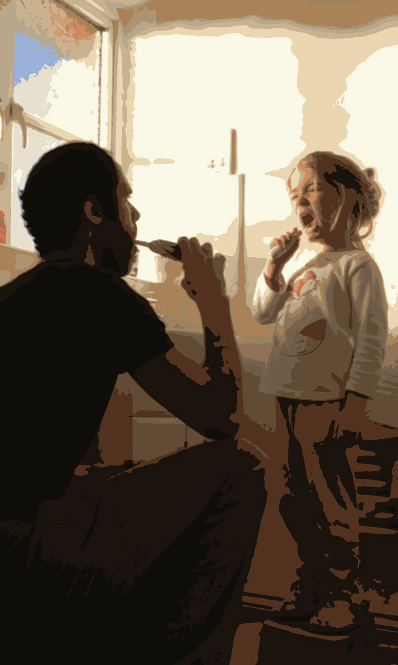 Father showing daughter how to brush her teeth