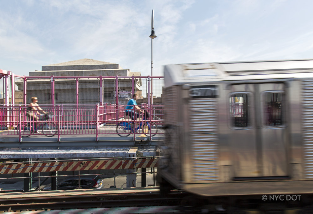 Train passing in front of cyclists on Williamsburg Bridge