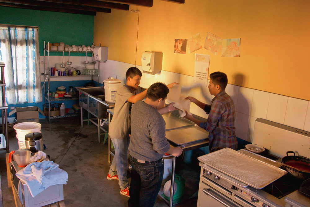 THREE STAFF MEMBERS AT LOS PATOJOS HELP PREPARE LUNCH IN JOCOTENANGO, GUATEMALA ON JAN. 12 FOR ANYONE WHO IS AT THE SCHOOL THAT DAY. MOST OF THE YOUNGER MALE TEACHERS HELP PREPARE FOOD TOGETHER.