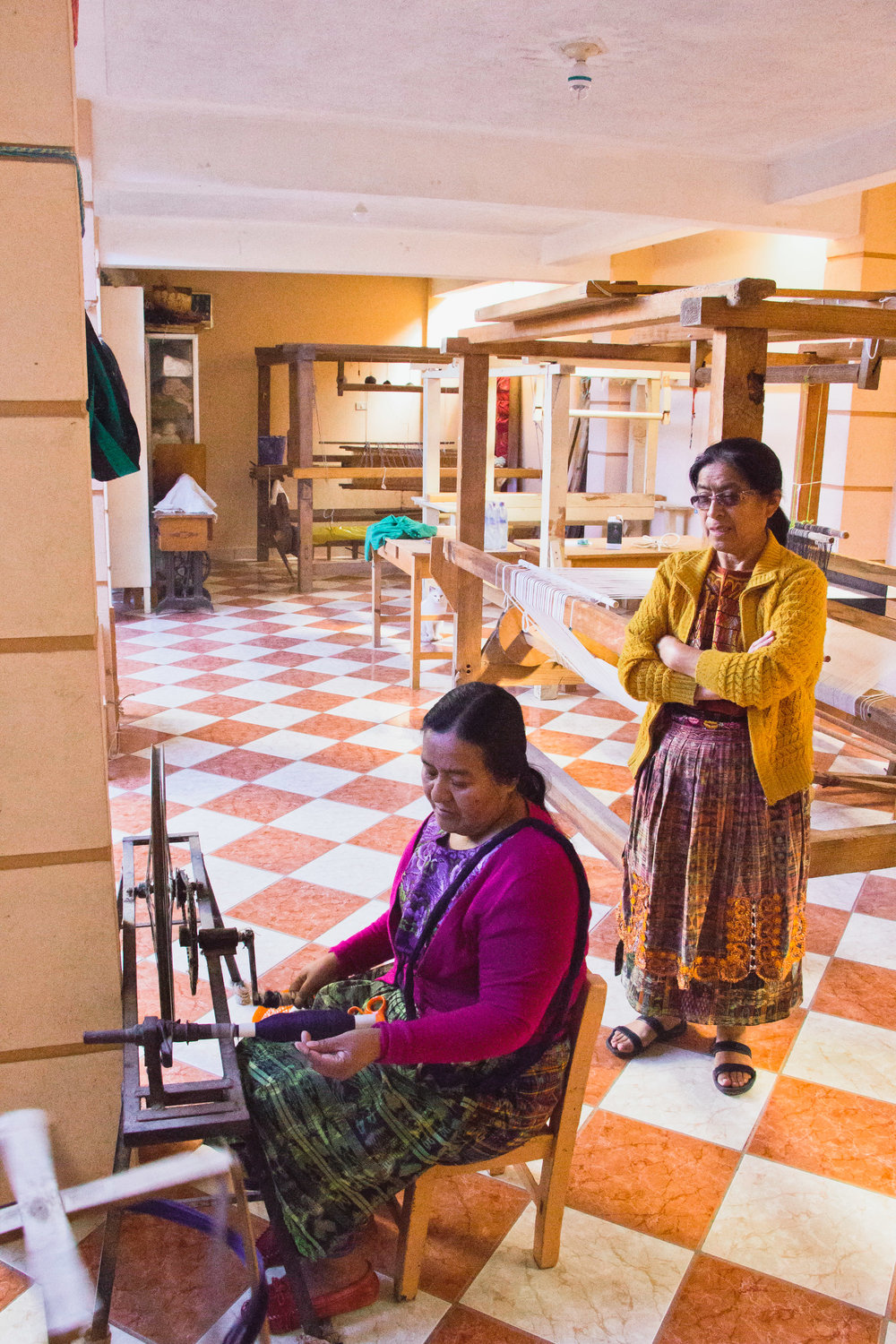 LIDIA SERECH CUTZAL OVERSEES CO-WORKER ESPERANZA AS SHE SPOOLS THE THREAD IN THE WORKSHOP OF THEIR HOME COMALAPA, GUATEMALA ON JAN. 12. THE FRIENDS MET NEARLY THIRTY YEARS AGO.