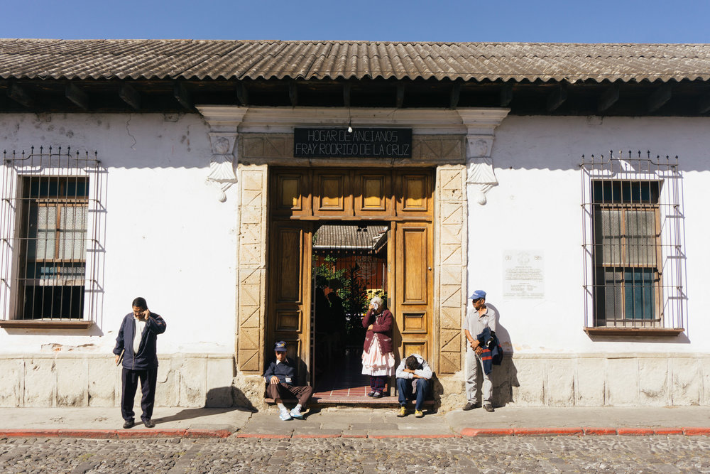 ANTIGUA RESIDENTS SIT OUTSIDE OF HOGAR DE ANCIANOS FRAY RODRIGO DE LA CRUZ IN THE LITTLE SHADE PROVIDED BY THE ROOF ON JAN. 17.