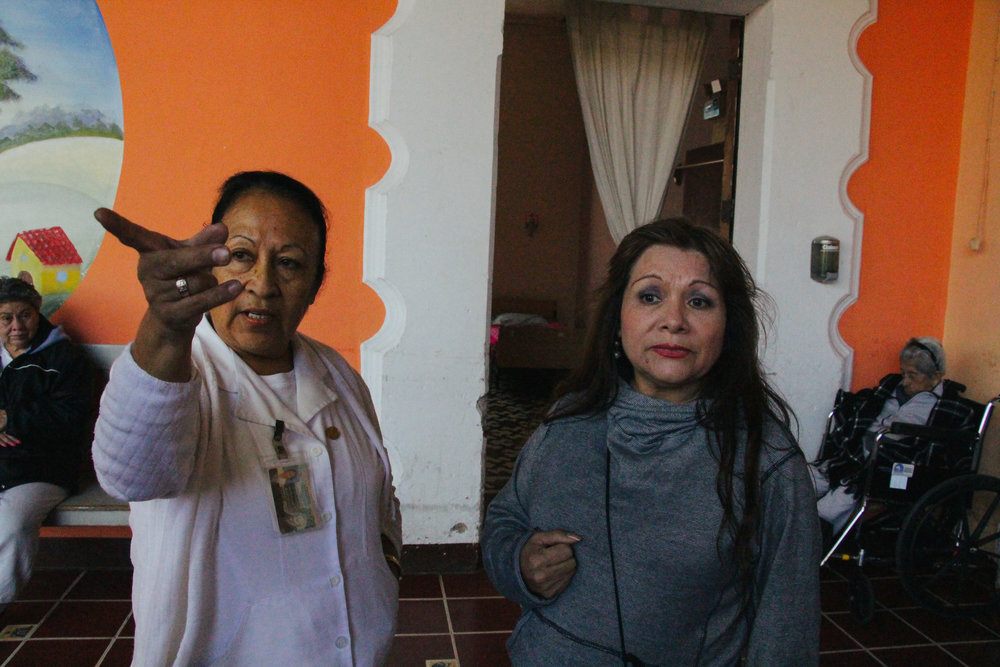 LIDIA ESCOBEDO INTERACTS WITH HOGAR DE ANCIANOS HEAD NURSE MAYDA ELIZABETH BARRIOS OROZCO ON JAN. 17. ESCOBEDO WORKS CLOSELY WITH DOCTORS AND NURSES TO ENSURE HER PATIENTS RECEIVE WELL-ROUNDED CARE.