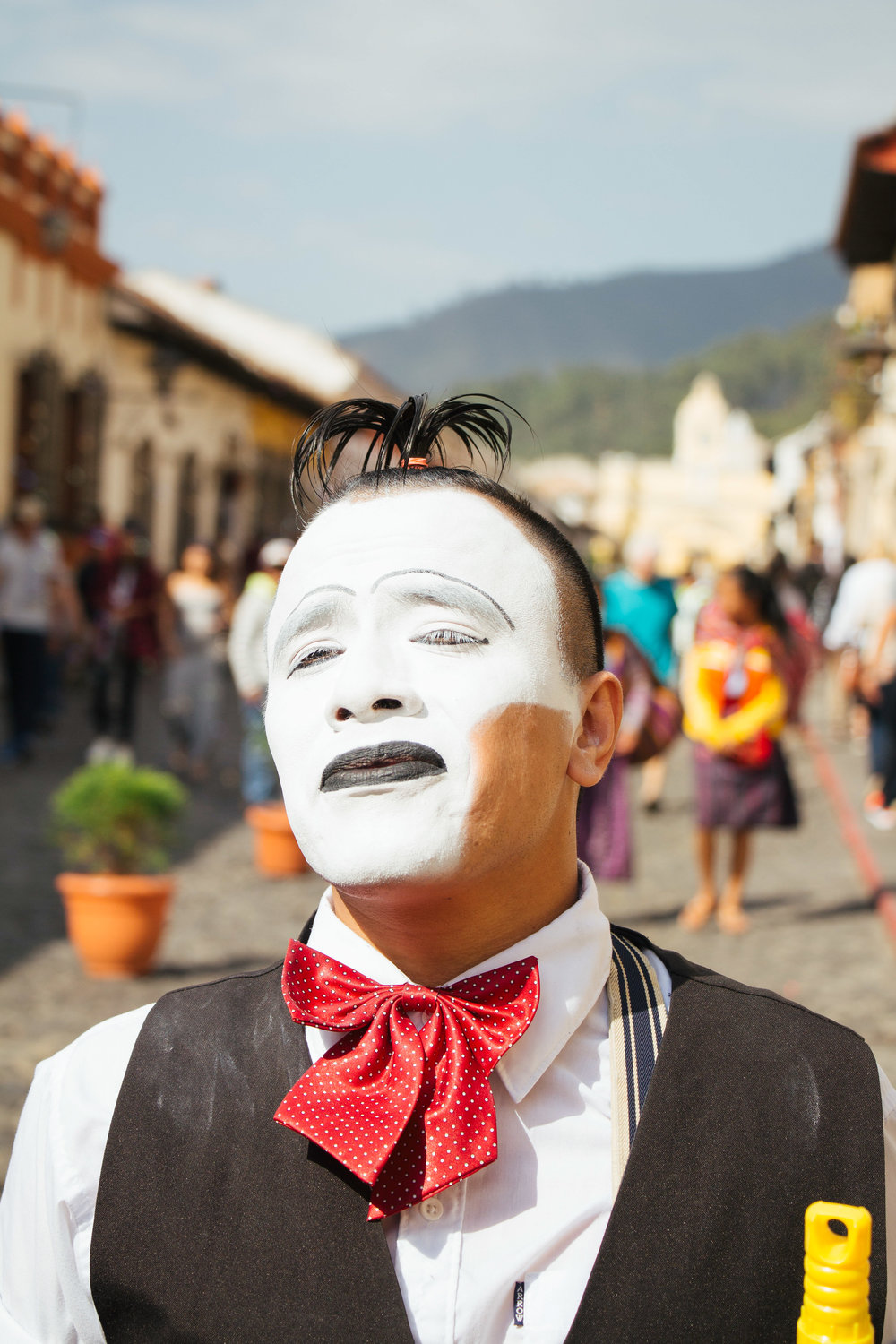 JUAN ESTUARDO TACEN PEREZ POSES DURING A PERFORMANCE ON 5A AVENIDA NORTE IN ANTIGUA, GUATEMALA JAN. 7. TACEN INTENTIONALLY DOES NOT PAINT ONE QUARTER OF HIS LEFT CHEEK TO CREATE A NEW PERSPECTIVE AND OUTLOOK ON STREET PERFORMERS.