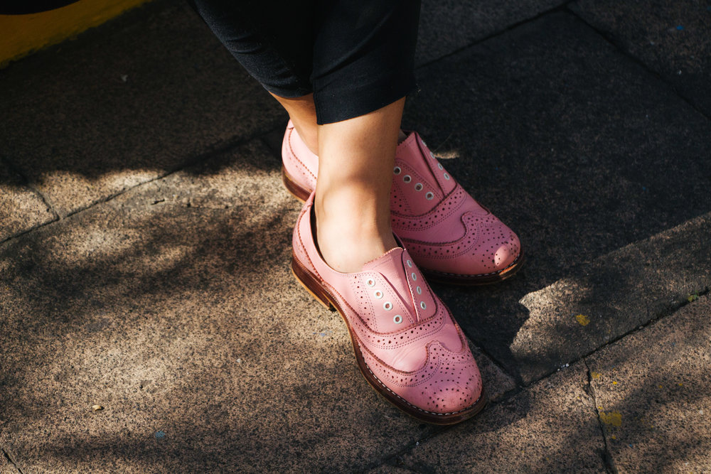 CRISTHA FUENTES SHOWS OFF HER PINK OXFORDS OUTSIDE OF SIMPLE, A STORE IN GUATEMALA CITY THAT SELLS HER DESIGNS. 60 PERCENT OF THE PROFITS FROM THE OXFORDS GO TOWARD SUPPORTING THE NATIONAL BREAST CANCER FUND.