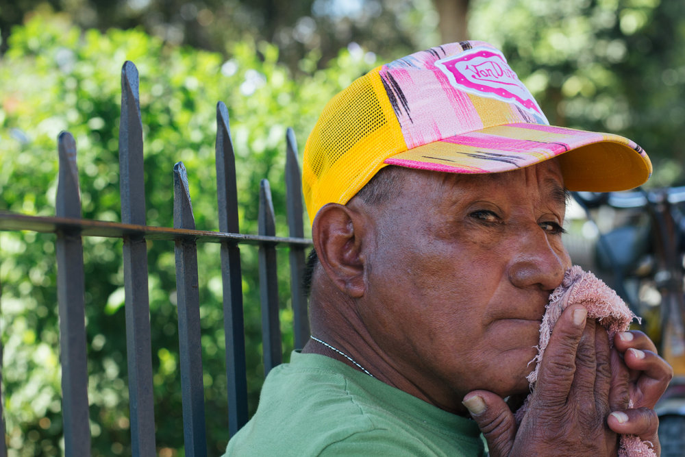 TOMAS LOPEZ RESTS ON THE CURB AND LEANS BACK ON THE FENCE TO ESCAPE THE SUN IN CENTRAL PARK OF ANTIGUA, GUATEMALA. LOPEZ WORKED AS SECURITY OFFICER FOR 11 YEARS AT AN ATM NEAR CENTRAL PARK BEFORE SELLING ICE CREAM.