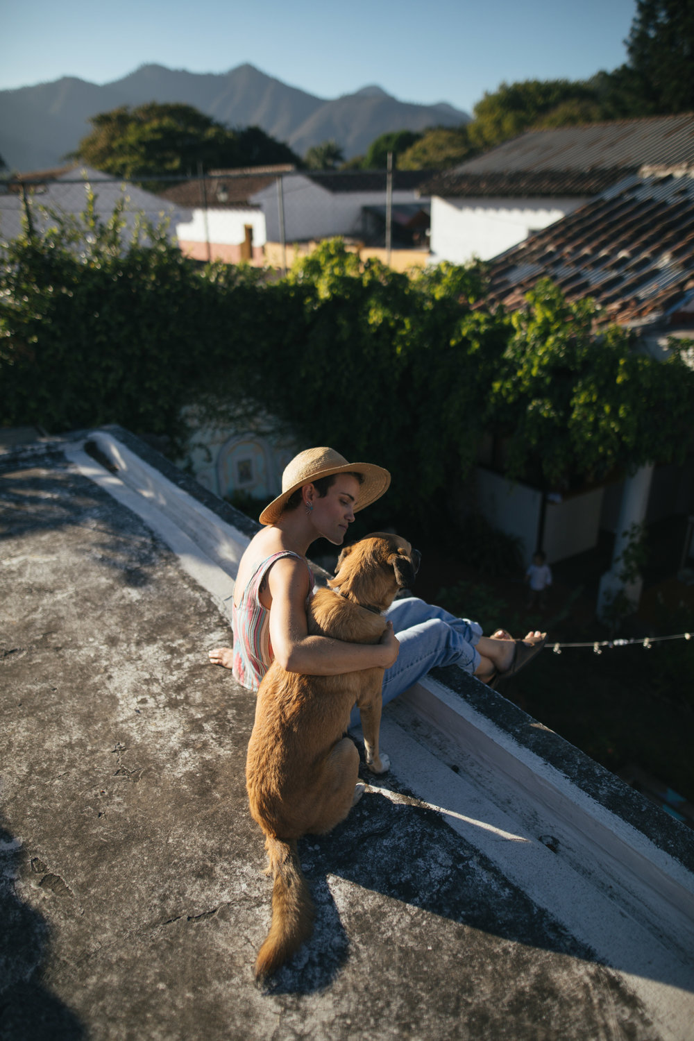 JESS BERCOVICI POSES WITH HER DOG GRUNER ON THE ROOFTOP OF STELA 9 AIRBNB AND BOUTIQUE OVERLOOKING ANTIGUA, GUATEMALA ON JAN. 13. BERCOVICI MOVED TO GUATEMALA A DECADE AGO, AND FOUNDED STELA 9 THREE YEARS LATER.