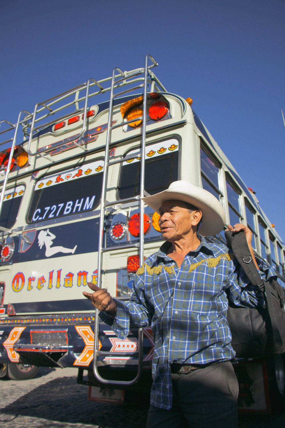 AN AYUDANTE CALLS OUT THE DESTINATION OF THE CHICKEN BUS IN THE ANTIGUA BUS TERMINAL ON JAN. 10. WHILE THEIR BUS IS PARKED IN A STATION, AYUDANTES WILL YELL THE NAME OF THEIR BUS'S DESTINATION IN HOPES OF GAINING MORE PASSENGERS.