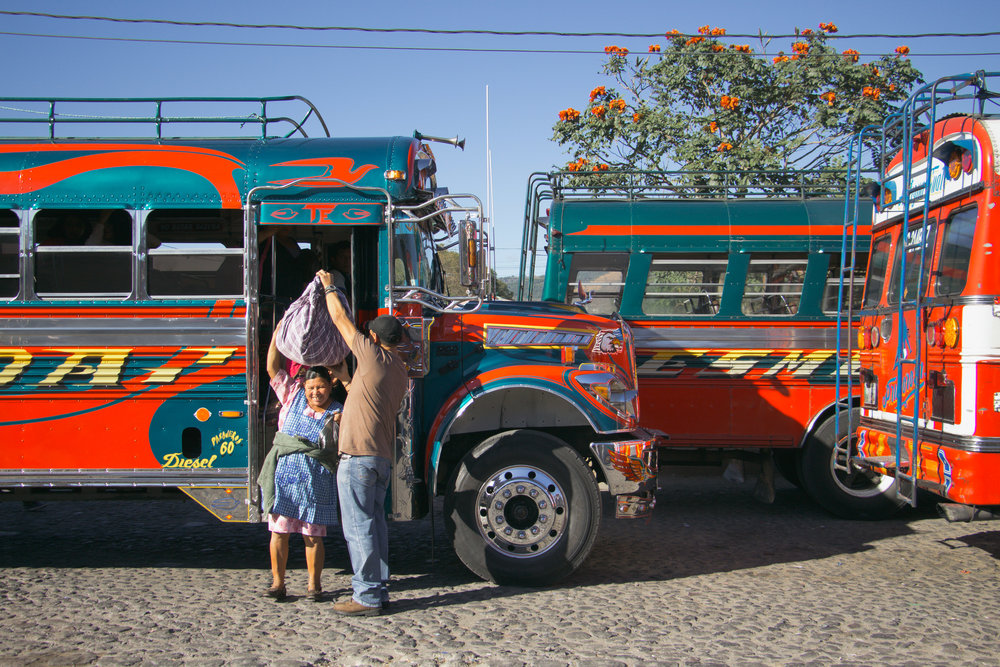 AN AYUDANTE ASSISTS A WOMAN AS SHE UNBOARDS A CHICKEN BUS IN THE ANTIGUA BUS TERMINAL ON JAN. 10. AYUDANTES ARE EXPECTED TO HELP PASSENGERS WITH THEIR LUGGAGE, WHEN THEY BOARD AND WHEN THEY LEAVE.