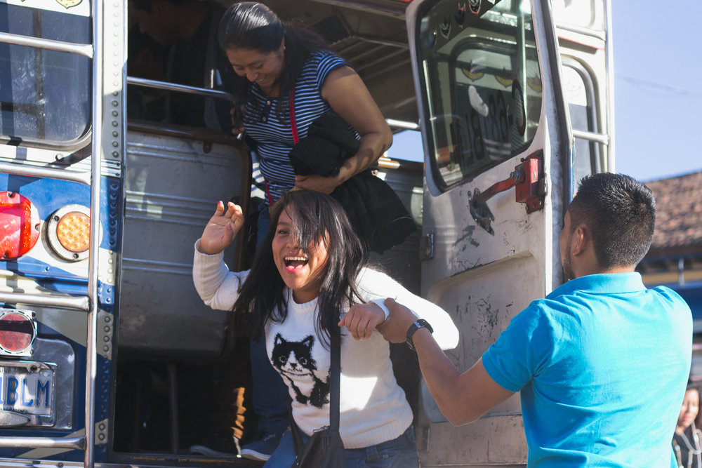 A COMMUTER LAUGHS AS SHE STEPS OFF A CHICKEN BUS WITH AN AYUDANTE CLOSE BY, HELPING HER DOWN IN THE ANTIGUA BUS TERMINAL ON JAN. 10. CHICKEN BUSES USE BOTH THE SIDE AND BACK DOORS OF THEIR REPURPOSED SCHOOL BUSES.