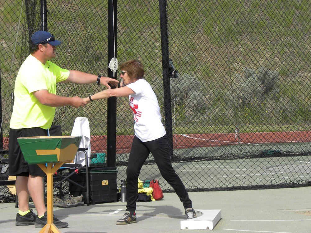 Gabriella being coached by Dylan Armstrong in shot put.