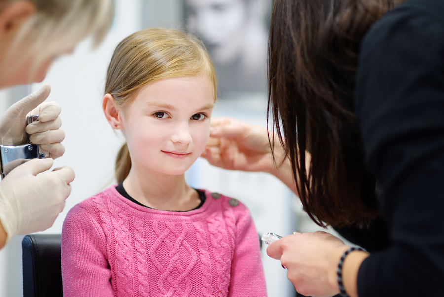 little girl getting her ears pierced by medical professionals