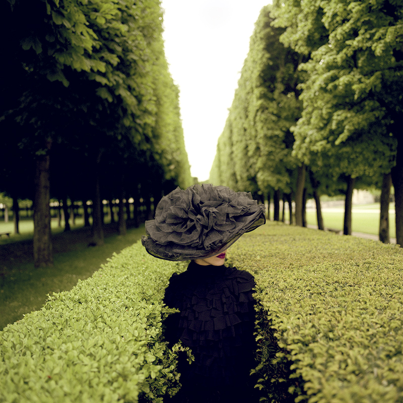 RODNEY SMITH,  Woman With Hat Between Hedges , Parc De Sceaux, France, 2004