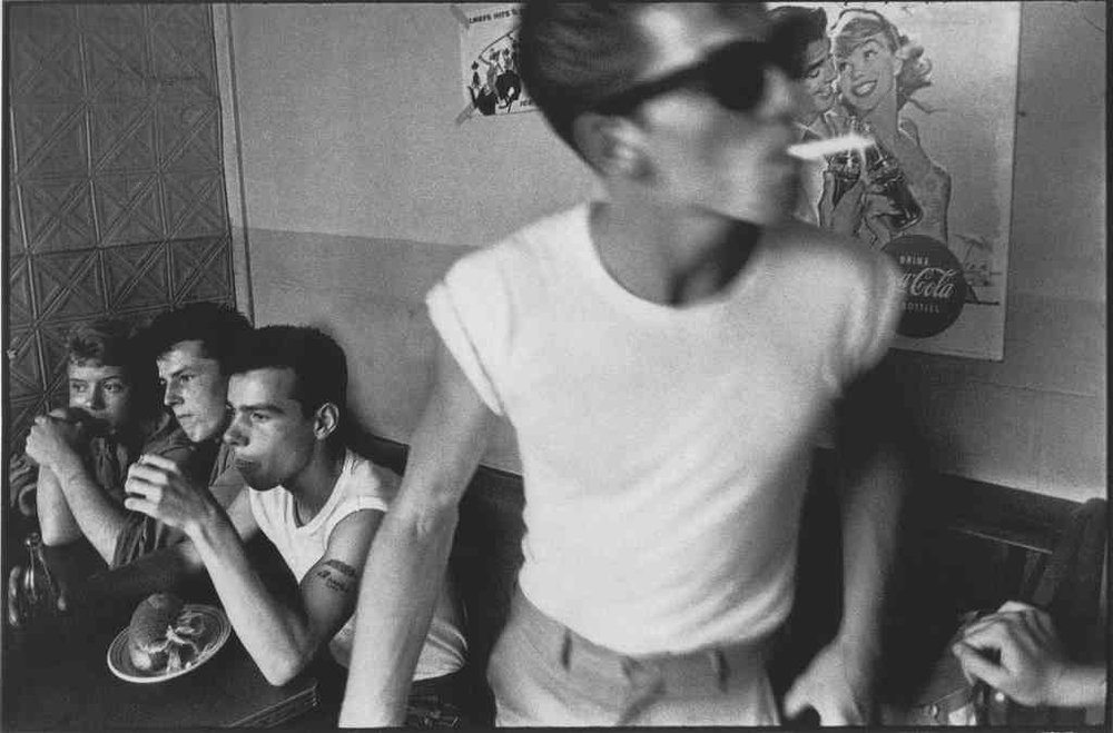 BRUCE DAVIDSON Brooklyn Gang (boys sitting at table, one standing with cigarette), 1959