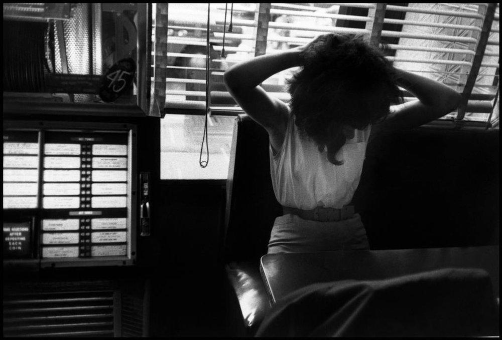 Girl Fixing Her Hair in Booth.jpg