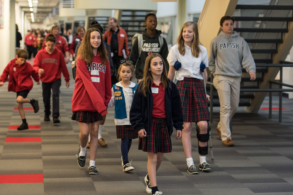 A group of Parish Episcopal Students ranging in ages walk down the Great Hall at the Midway campus of Parish Episcopal School in Dallas, Texas.