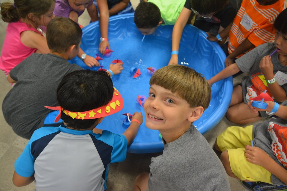 A boy looks back during an activity in a play pool during Parish Summer Day Camp in Dallas, Texas.