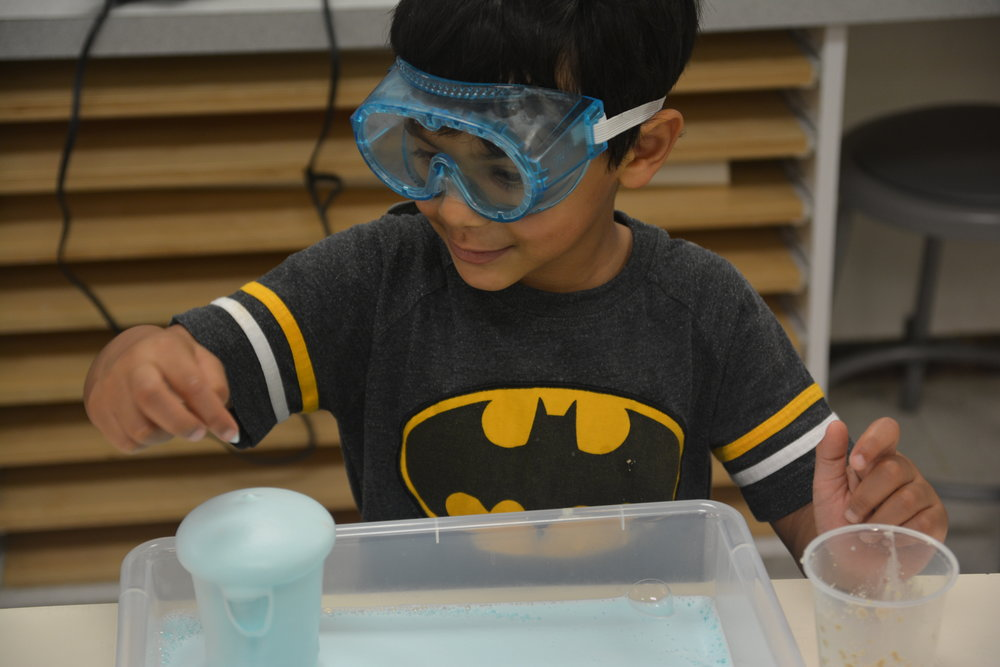 A boy makes a chemical reaction during a specialty day camp for preschool and elementary aged children through Parish Summer camps.