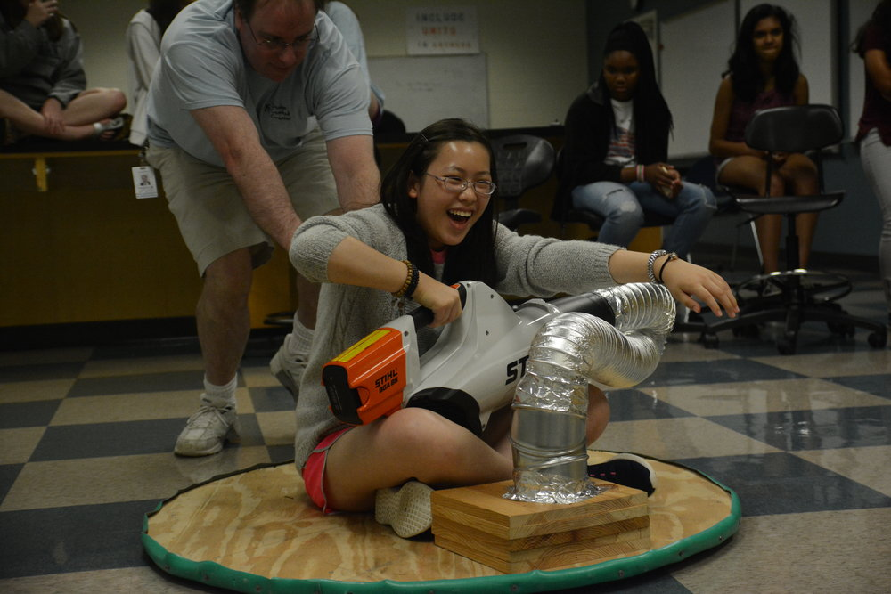 A high school student takes a ride on a homemade hovercraft during a STEM day camp through Parish Summer in Dallas, Texas.