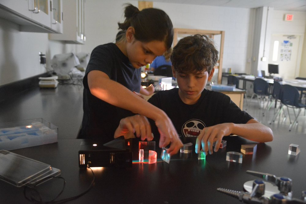 Two middle school boys direct light waves during one of Parish Summer's STEM day camps located in Dallas, Texas.