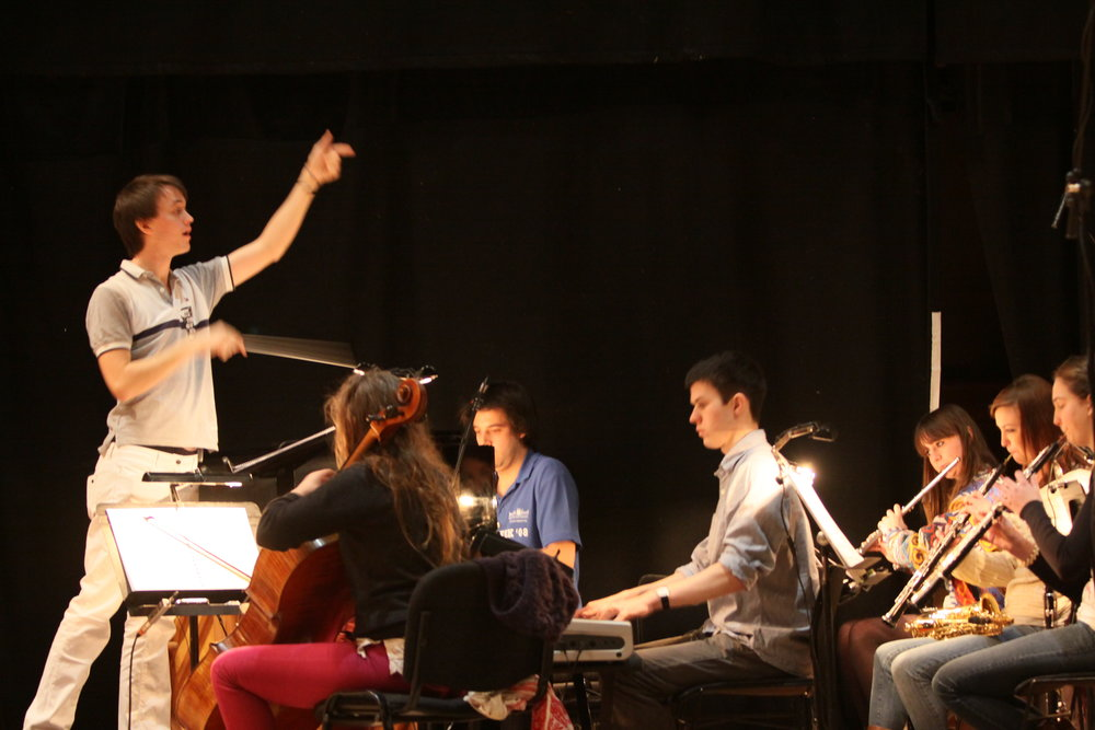 Jude conducting The Forbidden Fruit orchestra, Brighton Festival, Brighton Dome, composed by Jude Obermüller (photo by Sarah Sutherland-Rowe)