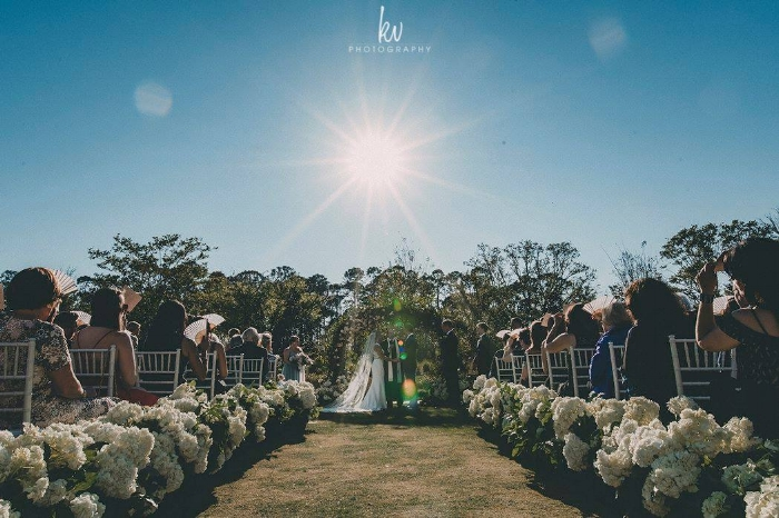 central florida sunset wedding ceremony - greenery wedding arch - beautiful aisle decor- lisa stoner weddings- ceremony decor.jpg