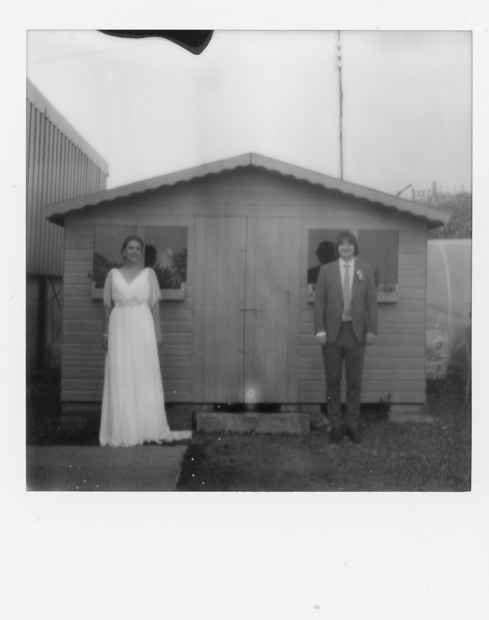 Lucy and Marc stand like a Wes Anderson pose for a black and white Polaroid at Wellbeing farm Bolton