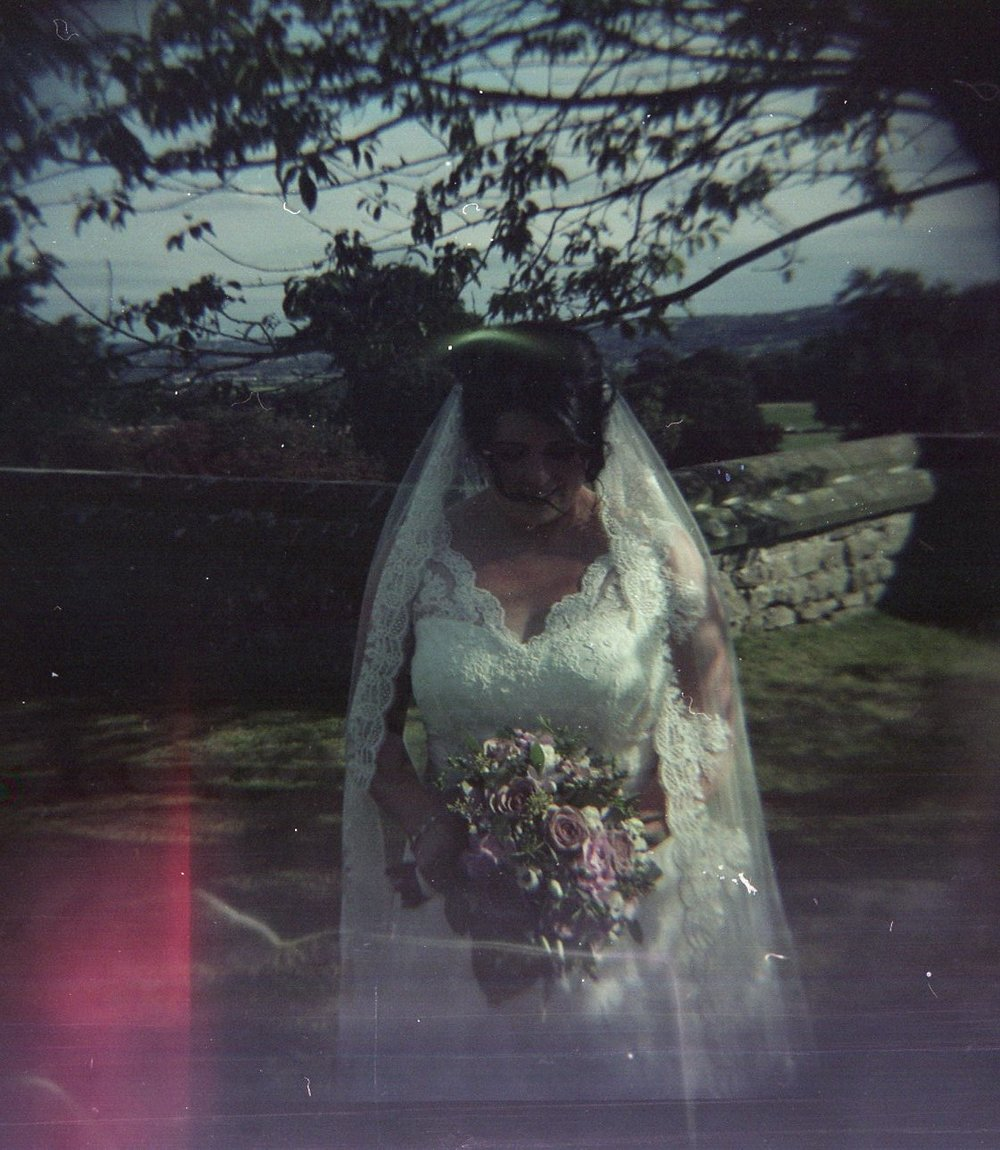 Catherine looking down outside getting married in a church. Taken with Diana Camera F+