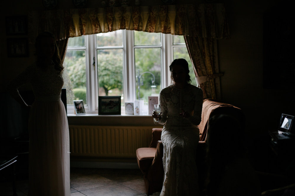 Bride sat down with a drink having a quiet moment before her wedding. Silhouetted with dark shadows against the living room window