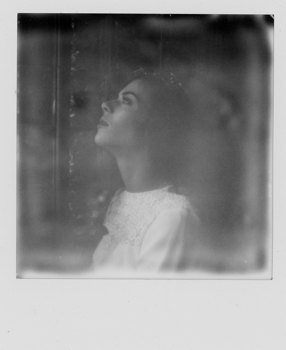Model Freya is wearing a Frock and Soul wedding dress at Victoria Baths in Manchester. She is looking up at the window with the light on her face. This image is on a black and white Polaroid taken with an SX-70 Camera.