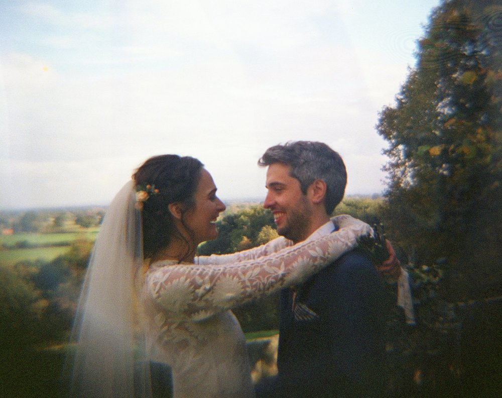Camilla and John laugh in the golden light together. The photo is taken with a Diana F+ Lomography medium format camera so its fuzzy and beautiful. Camilla's wedding dress is embroidered and is stunning on this bohemian bride. There vibrant beautiful trees in the background and clouds in the sky.