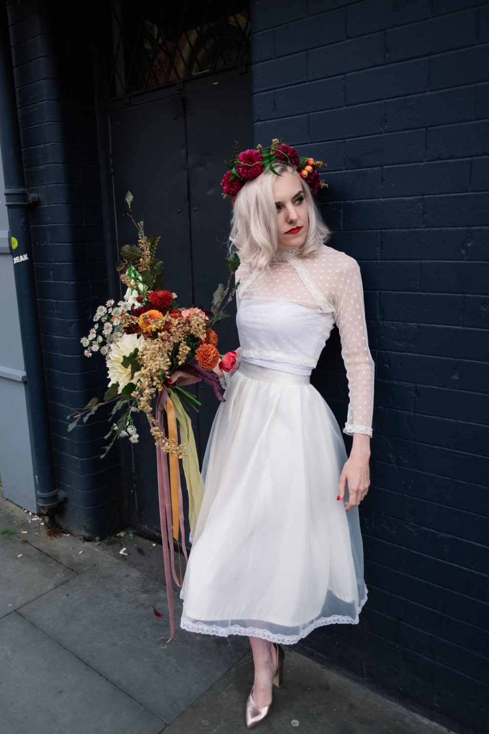 Model Martha stands against a dark blue wall with her beautiful Wedding Bouquet