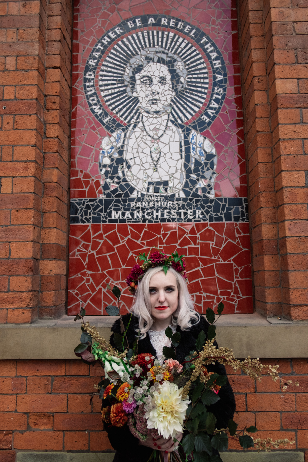 Martha stands in front of the Emmeline Pankhurst tribute Afflecks palace in Manchester wearing a flower crown and wedding dress by Wilderness bride