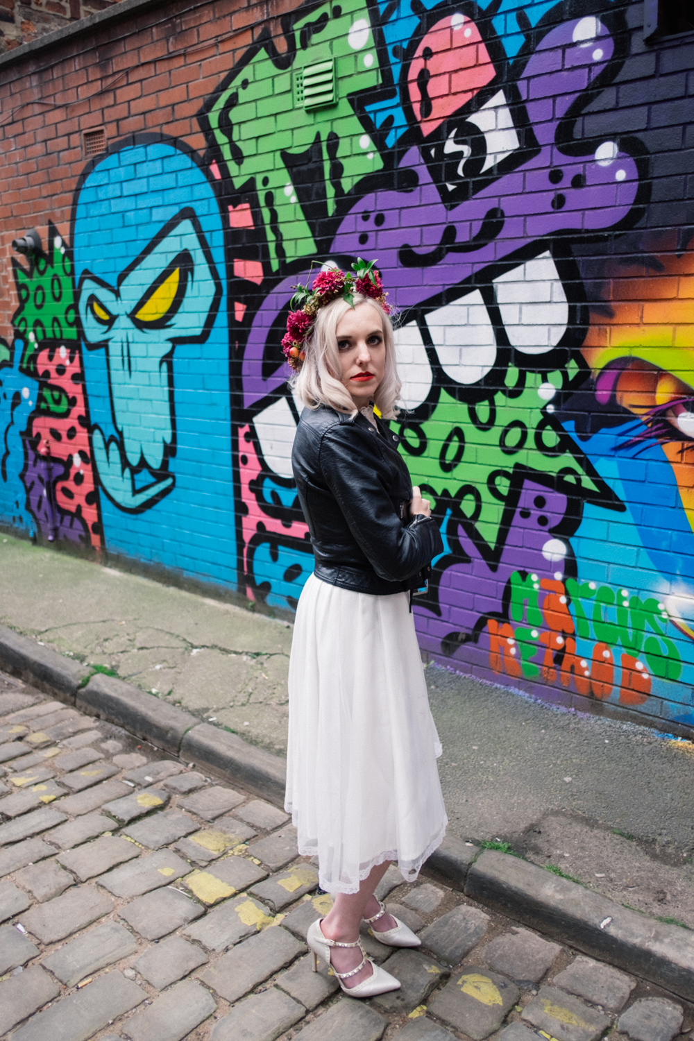 Wearing a leather jacket and looking straight at the camera model martha is stood in front of some really colourful grafitti in the northern quarter