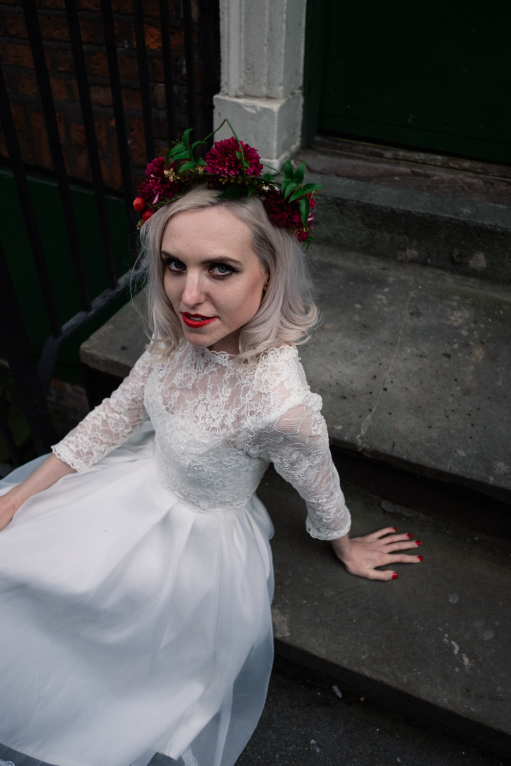 Grunge bride Martha sat on steps in Northern Quarter Manchester with Fletcher and Foley flower crown