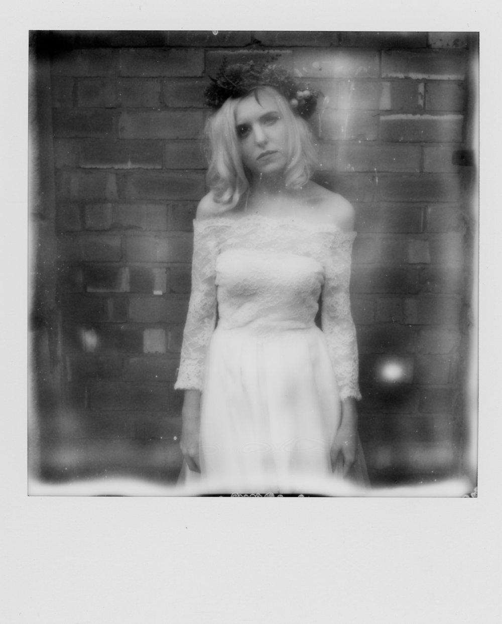 Monochrome polaroid of Martha stood in a deadpan stance looking towards the camera in her Wilderness Bride Dress