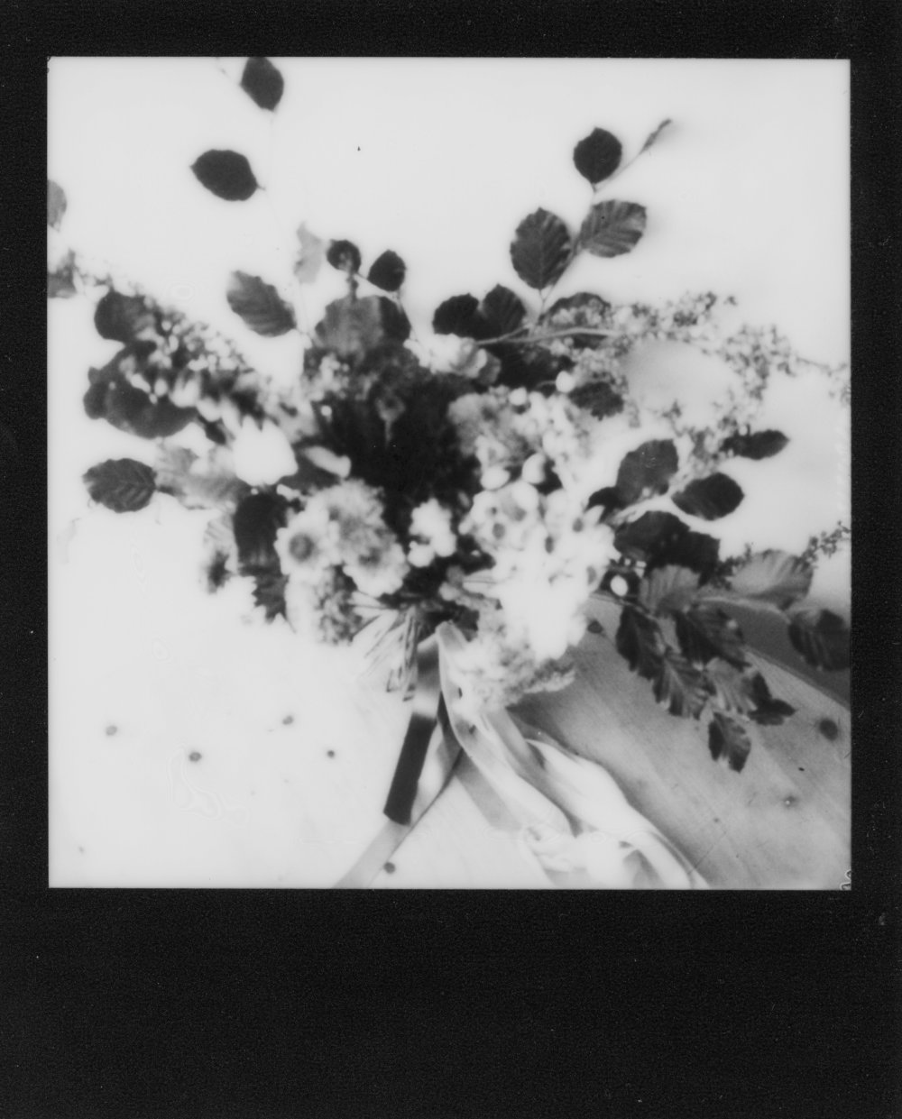 Monochrome Polaroid of Fletcher and Foley Bouquet, with dahlia's and carnations