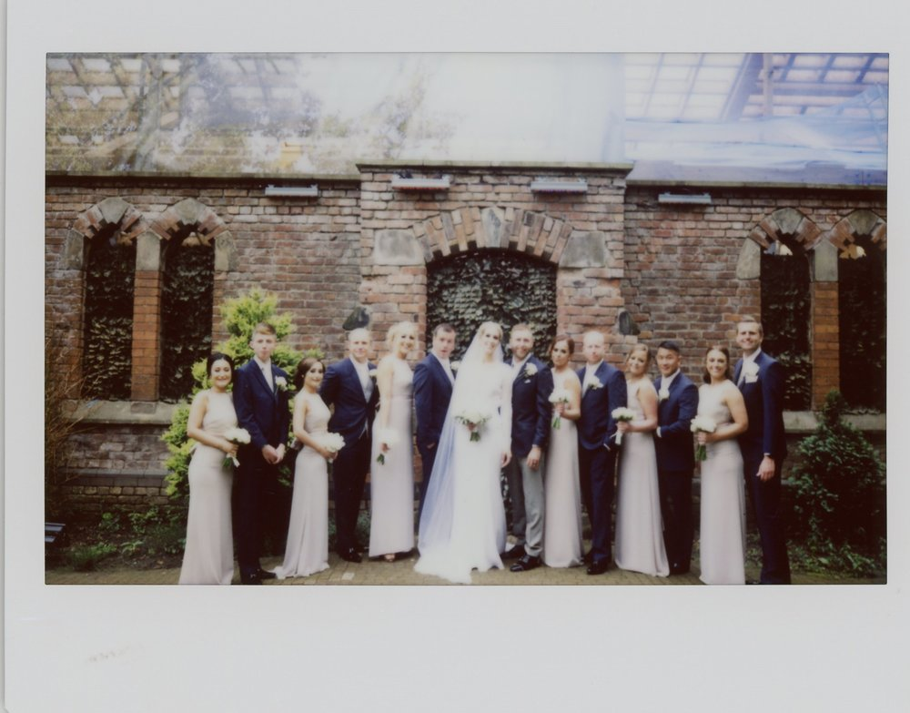 Instax of Jo and Dan havinga group photo at the monastery manchester