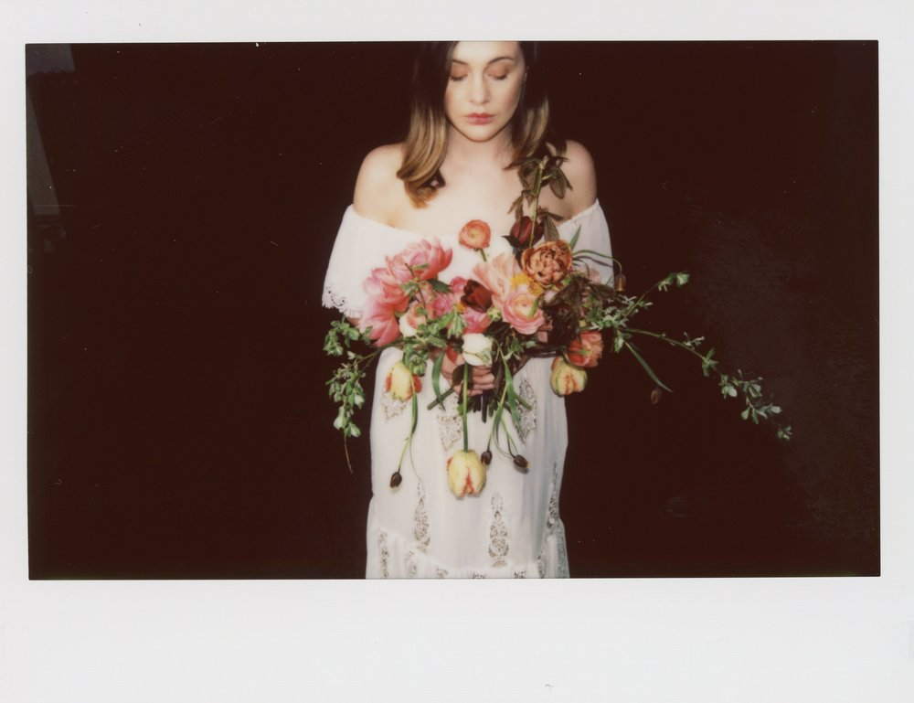 Model Alicia is holding a bouquet of flowers with Peonies looking down. She is wearing an off the shoulder Francis Bridal Wedding dress called Aroha. This photo is taken with an instax wide camera