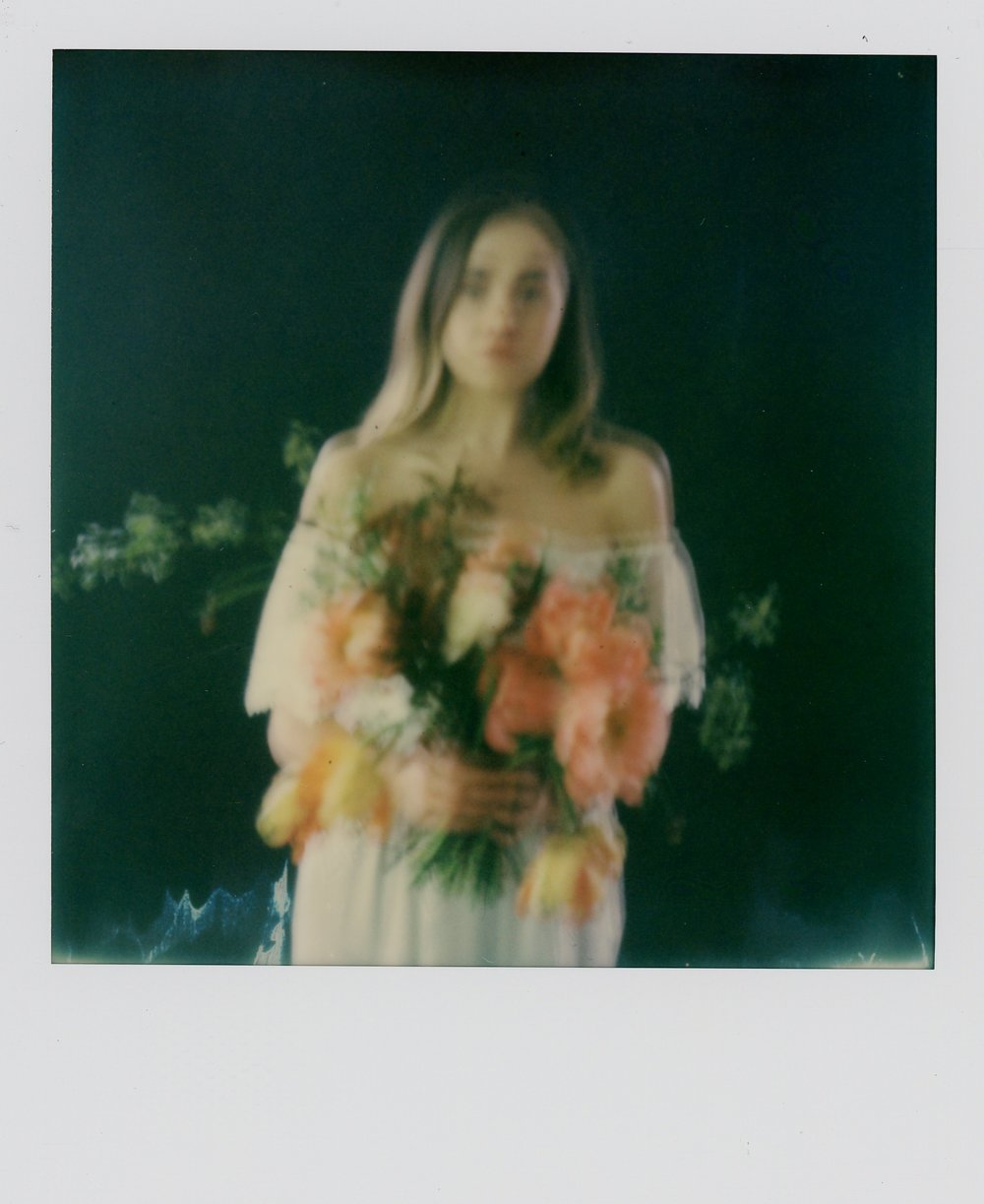A blurry colour Polaroid of Alicia looking at the camera holding an arrangement of flowers from The Yorkshire Flower Patch