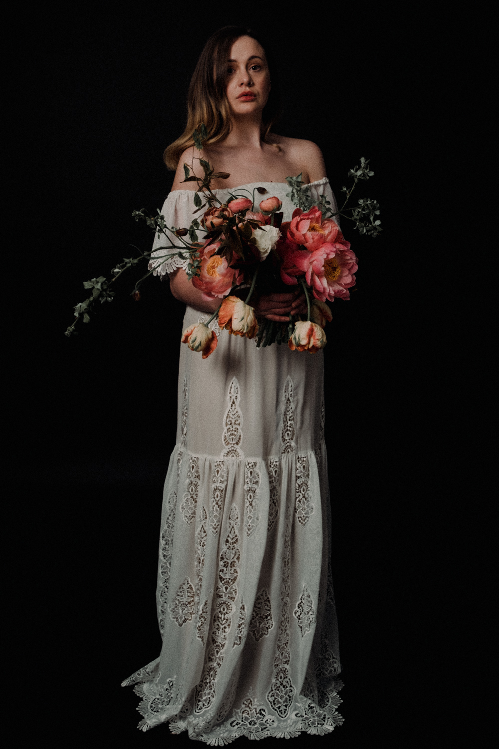 Alicia stands with the bouquet of flowers featuring Peonies, Tulips and Ranuculus' looking directly at the camera