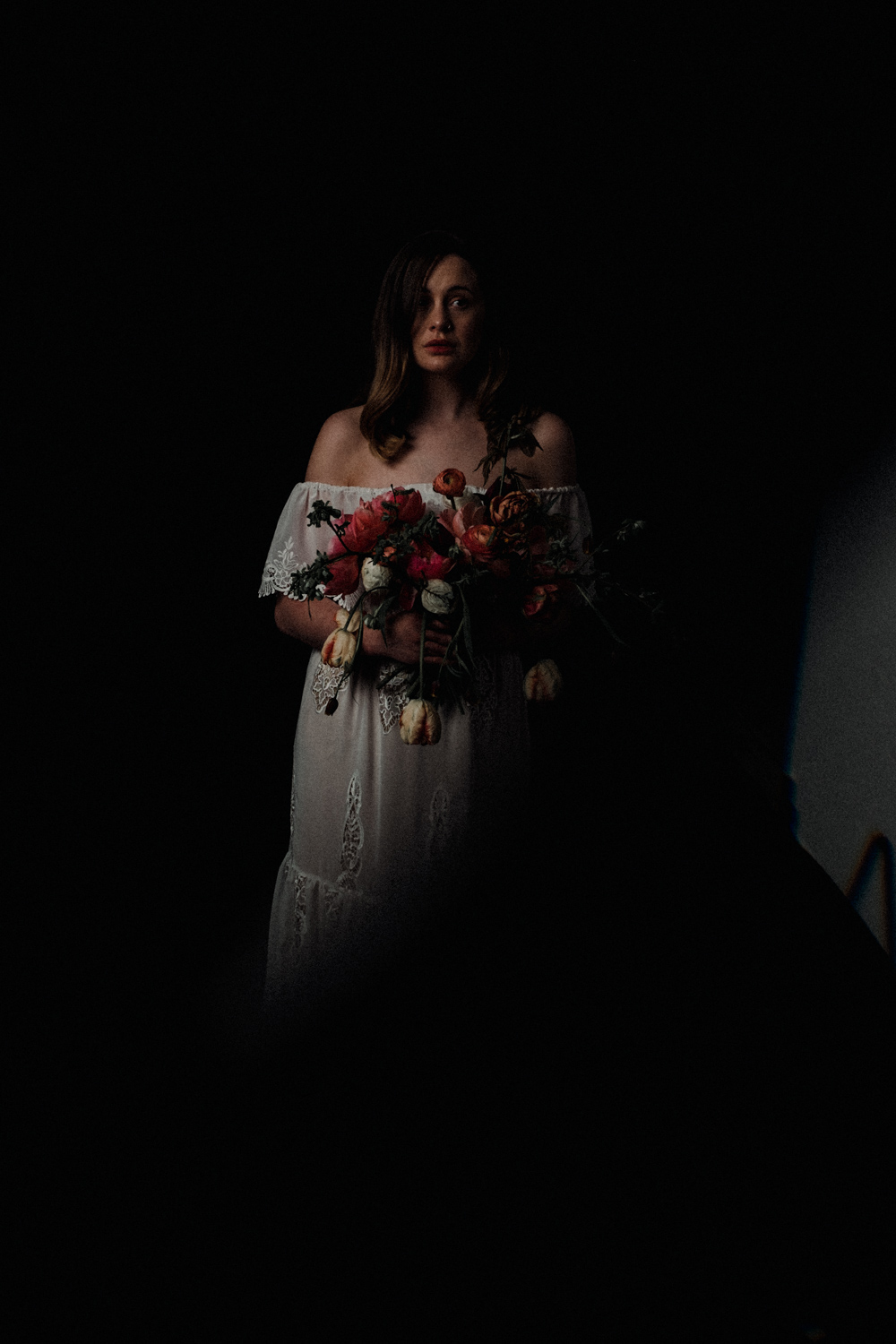 Alicia is stood in the shadows with her wedding bouquet