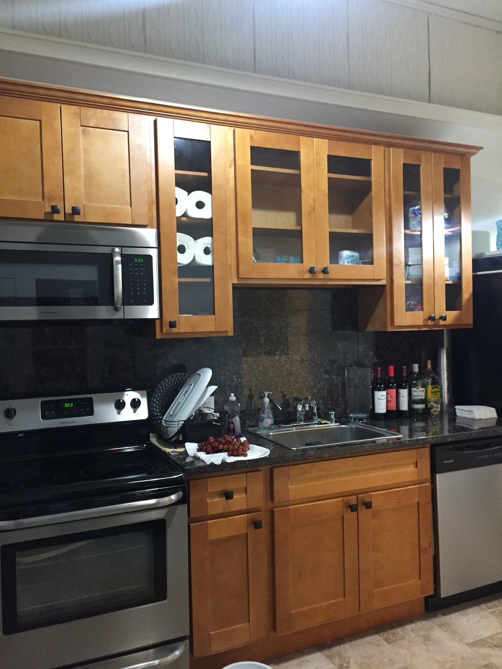 Kitchen with brand new stainless appliances, full size refrigerator and granite counter tops.