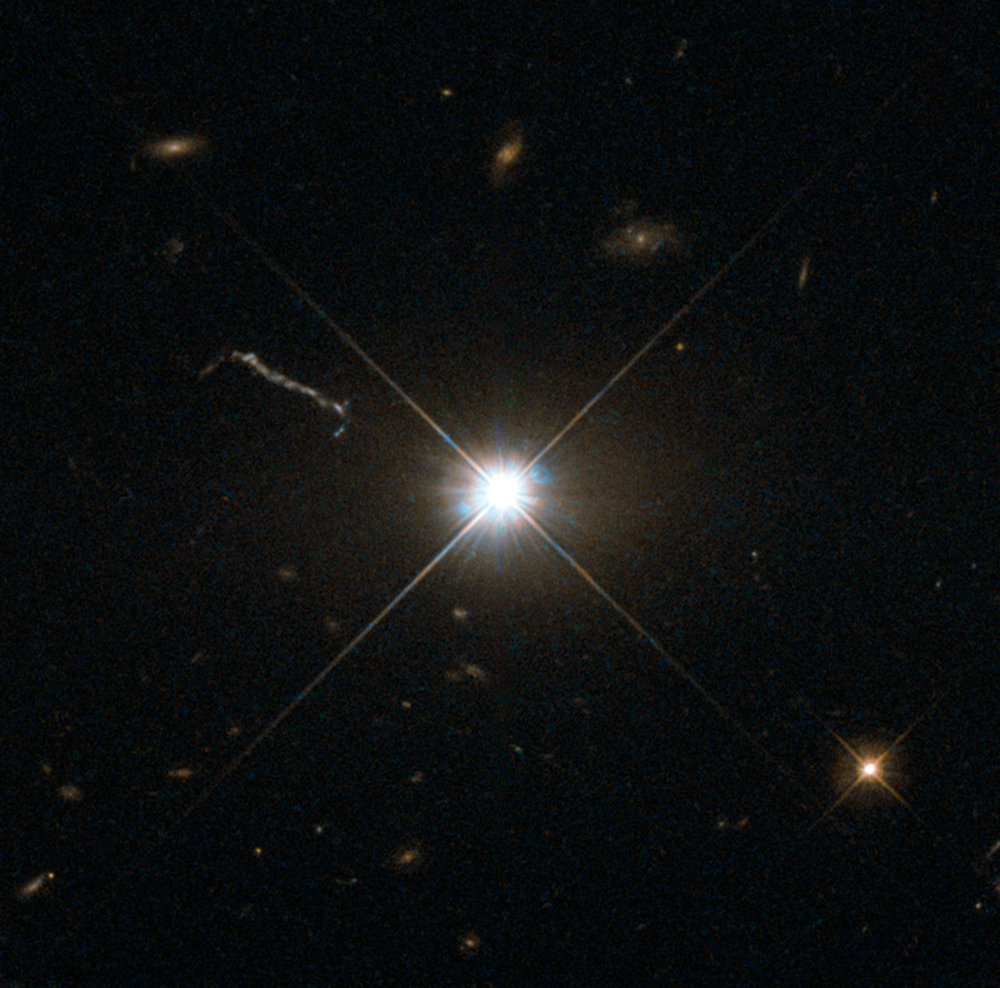 "Figure 3: ""This image from Hubble's Wide Field and Planetary Camera 2 (WFPC2) is likely the best of ancient and brilliant quasar 3C 273, which resides in a giant elliptical galaxy in the constellation of Virgo (The Virgin). Its light has taken some 2.5 billion years to reach us. Despite this great distance, it is still one of the closest quasars to our home. It was the first quasar ever to be identified, and was discovered in the early 1960s by astronomer Allan Sandage. The term quasar is an abbreviation of the phrase ""quasi-stellar radio source"", as they appear to be star-like on the sky. In fact, quasars are the intensely powerful centres of distant, active galaxies, powered by a huge disc of particles surrounding a supermassive black hole. As material from this disc falls inwards, some quasars — including 3C 273 — have been observed to fire off super-fast jets into the surrounding space. In this picture, one of these jets appears as a cloudy streak, measuring some 200 000 light-years in length. Quasars are capable of emitting hundreds or even thousands of times the entire energy output of our galaxy, making them some of the most luminous and energetic objects in the entire Universe. Of these very bright objects, 3C 273 is the brightest in our skies. If it was located 30 light-years from our own planet — roughly seven times the distance between Earth and Proxima Centauri, the nearest star to us after the Sun — it would still appear as bright as the Sun in the sky. WFPC2 was installed on Hubble during shuttle mission STS-125. It is the size of a small piano and was capable of seeing images in the visible, near-ultraviolet, and near-infrared parts of the spectrum.""\(^{[3]}\)  Image Credit: ESA/Hubble [CC BY 4.0 (http://creativecommons.org/licenses/by/4.0)], via Wikimedia Commons"