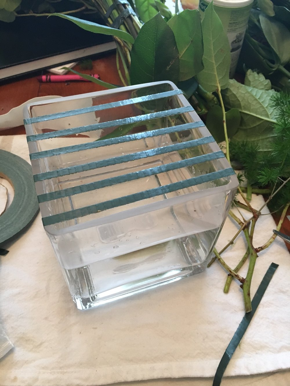 Here is a basic glass cube vase, usually about $4-$5 per vase. I like to use thin floral sticky tape to create a grid on the mouth of the vase. This gives the stems something to grab hold of and also makes keeping arrangements symmetrical a bit easier.