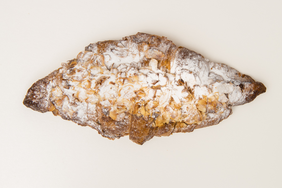Almond Croissant  - A baked croissant filled with almond cream, topped with flaked almonds and finally dusted with powdered sugar.