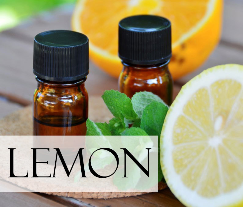two vials of lemon essential oil on a table with a lemon half