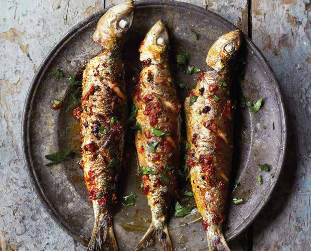 delicious barbecued harissa sardines on a place. this is a healthy option for your next barbecue