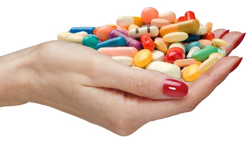 a hand holding supplement pills