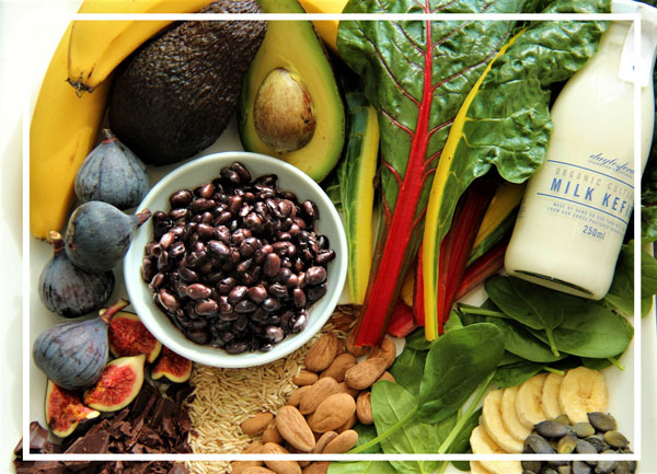 A selection of magnesium-rich foods, including dark chocolate, milk, spinach, figs, brown rice, almonds, bananas, swiss chard, black beans and avocados. Photo by Alicia Bennett